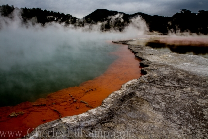 Steam rises above the brightly colored mineral deposits of Champagne Lake